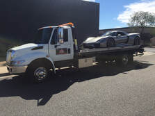 silver luxury car on tow truck