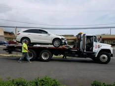 white suv car getting towed by white truck